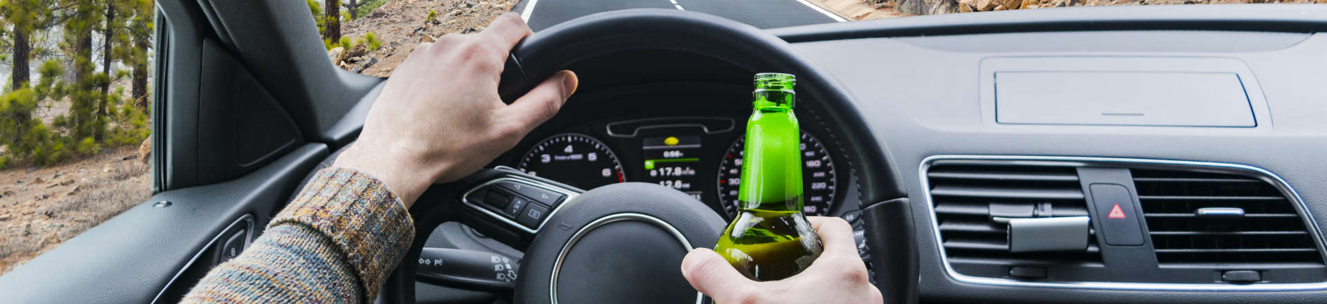 a driving person with a bottle of beer in their hand
