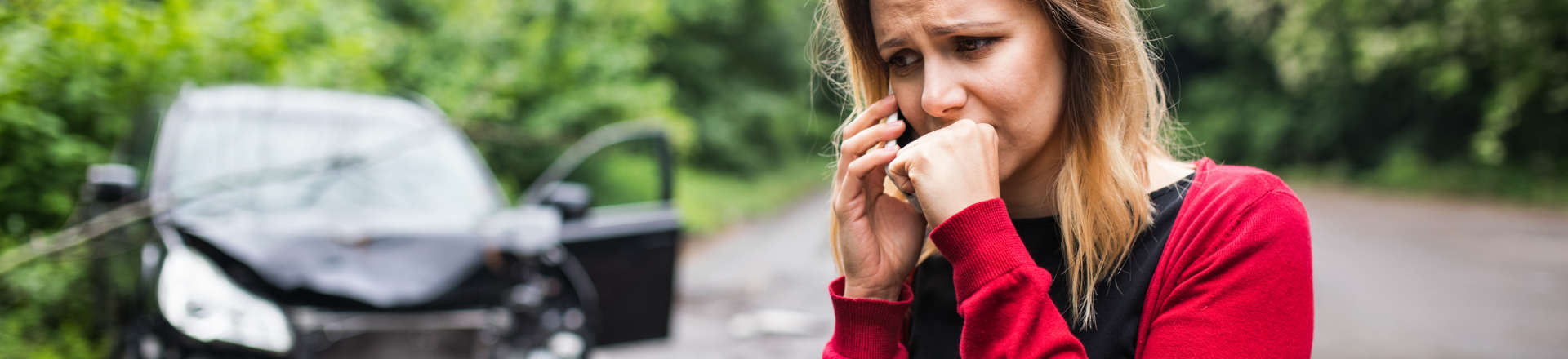 a stressed woman outside a crashed car talking on the phone