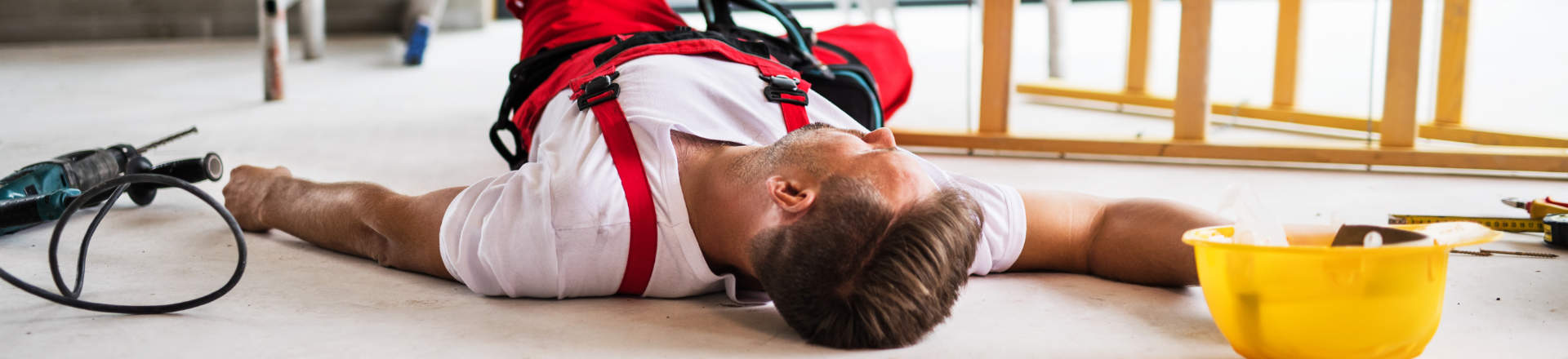an injured man lying on the floor after having fallen off a defective ladder